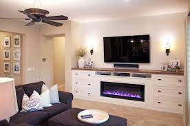white entertainment center with fireplace shaplap wall