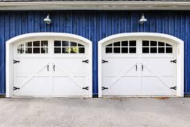 striking white carriage style garage doors on blue home