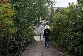 a woman takes a stroll on west lane foot path in the upper rockridge neighborhood in