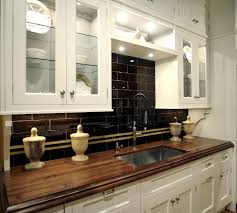 brown reclaimed wood countertops for white kitchen cabinets having square undermount sink and dark tile backsplash