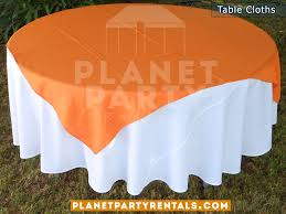 round table with white table cloth and orange overlay runner