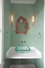 small chic powder room is clad in mint green grasscloth lined with a driftwood mirror illuminated by ziyi sconces situated over a white floating vanity