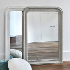 rectangular wooden wall mirror with curved corners to top and beaded design to frame in a
