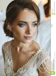 portrait of fashionable beautiful and sensual brown haired model with professional bright makeup and blue eyes in stylish lace dress