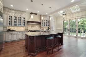 beautiful white kitchen cabinets: luxury white kitchen with elegant glass faced cabinetry and wood flooring