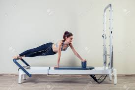 pilates reformer workout exercises woman brunette at gym indoor stock photo 47935407