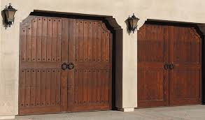 two wooden carriage house garage doors are outlined with decorative wrought iron embellishments and have wrought