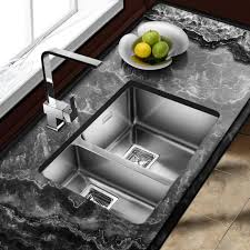 one and half bowl stainless steel undermount kitchen sink with modern faucet on black marble