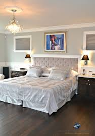 benjamin moore revere pewter in glam master bedroom with white wainscoting and crystal teardrop chandelier