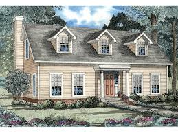 cape cod new england style home with triple dormers