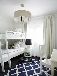 white and blue boys room with jonathan adler channing end table topped with a jonathan adler white horse head table lamp beside white bunk beds dressed in