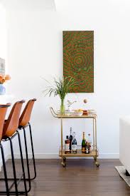slim painting above a bar cart
