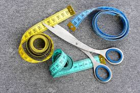 Scissors With Light Rolls Of Colorful Measure Tape With Metallic Scissors On Light