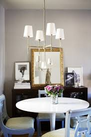 eclectic dining space with ikea docksta table craiglist chairs gray walls black buffet gold mirror and thomas o brien bryant chandelier