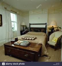 Small Armchair For Bedroom Antique Wooden Chest And Small Cream Armchair In Bedroom With