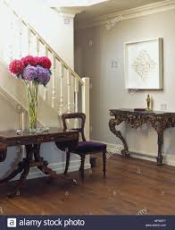 side table for hallway. A Traditional Hallway With Large Vase Of Flowers On Decorative Wooden Side Table Below Staircase. For