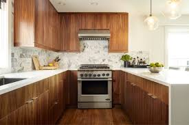 and white together along with stainless steel appliances and a natural stone backsplash for a wonderful textural effect the lighter wood countertop
