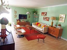 Mint green walls of this mid-century modern living room are balanced with a  red