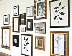 white frames mixed with gold frames and black white photos kids art on white and gold framed wall art with black and white vintage picture wall puck lights showcase art