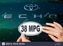 Close of a woman attaching a 38 miles per gallon fuel efficiency ...