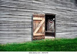 red barn doors. Old Weather-beaten Barn. A Door Is Open, Allowing The Viewer To See Red Barn Doors