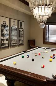 fantastic room features a tiered glass bottles chandelier arteriors stedman 5 light iron glass chandelier hanging over a pool table