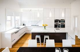 contrast between white kitchen design and wood laminate flooring