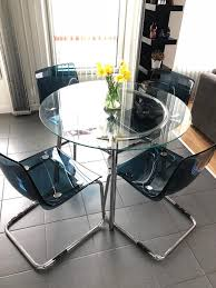 round glass table w 4 blue chairs
