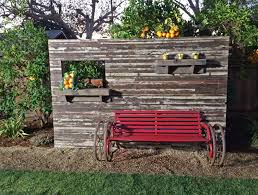 Privacy wall made with reclaimed wood with a repurposed bench supported by  reclaimed wagon wheels.