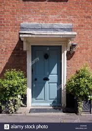 green shrubs in pots on either side of blue front door in brick country house