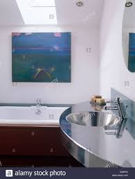 stainless steel washbasin and tap in modern bathroom with large painting above ed bath tub under skylight