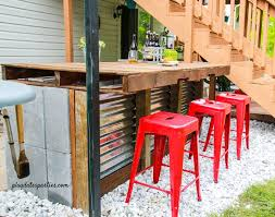 diy outdoor bar completed with bright red bar stools