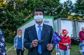 man wearing suit face mask holds small Editorial Stock Photo - Stock Image    Shutterstock