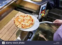 prepared pizza on a metal spatula is taken from the conveyor stock image