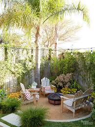 this fire pit area via bhg feels tropical but cozy tucked into the back corner of the yard outdoor string lights for the win i definitely want to