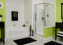 bathroom white bathtub and small glass shower stalls connected by black mats on the floor