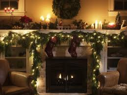 of fireplace decorating ideas for presenting hanging green pine leaves garland with white lighting and two red socks on white stone fireplace
