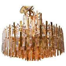brass chandelier composed of multiple suspended brass strips and crystal prisms for