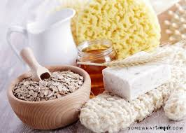 a bowl of oatmeal with a wooden scoop a jar of honey and a pitcher