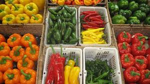 plastic and wood trays holding a variety of peppers
