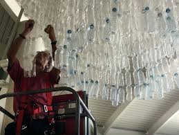 plastic bottle chandelier hanging in corpus airport photo engineer attaches some bottles to a chihuly