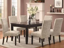 fancy dining room with upholstered chair also wood table bine marble top plus area rug and laminated floor high back chairs grey fabric along design