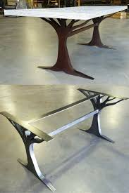 What an interesting custom table leg base. Made from metal. Love the tree.  Chair selection for the table should be careful to not block the design.