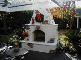 outdoor pergola with stucco fireplace and iron furniture