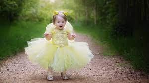 süßes Baby trägt gelbes Kleid, das auf ...