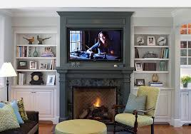 fireplace mantels with tv above giving the fireplace mantel and the tv backdrop a uniform look
