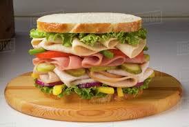 Large Chicken Ham And Turkey Sandwich With Veggies On White Bread