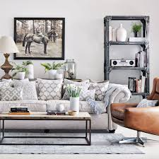 cream colored sofa with lots of patterned cushions in beige and white living