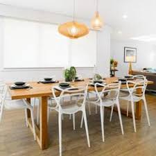 timber dining table with white chairs proving you don t have to furniture sets see all the photos of this open plan kitchen living dining area