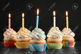 Birthday Cupcakes With Candles On Table Against Black Background